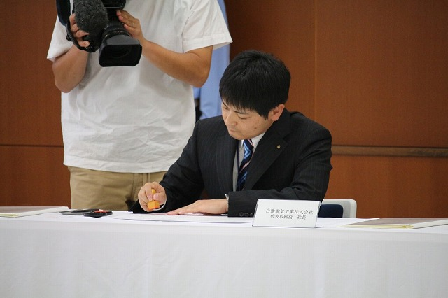 協定書に調印する沼田社長